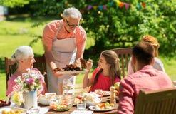 Familie die diner of barbecue hebben bij de zomertuin royalty-vrije stock afbeelding