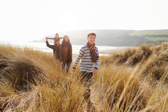 Familie die door Zandduinen lopen op de Winterstrand stock fotografie