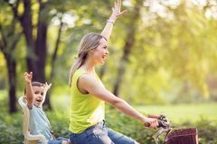 """Familie, die draußen †""""Mutter und Sohn auf Fahrrädern im Park radfährt Lizenzfreie Stockbilder"""