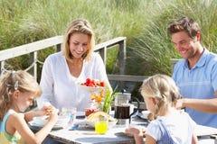 Familie, die draußen auf Ferien frühstückt stockbild