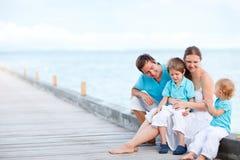 Familie, die draußen an der Küste sitzt Stockbilder