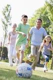 Familie, die draußen Fußball spielt und Spaß hat Stockfoto