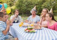 Familie, die draußen Geburtstag der kleinen Mädchen am Picknicktisch feiert Lizenzfreies Stockfoto