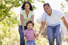 Familie, die draußen lächeln laufen lässt Stockfotografie