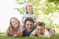 Familie, die draußen lächelnd liegt Stockfotos
