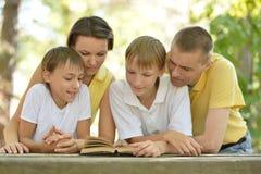 Familie, die draußen liest Lizenzfreie Stockbilder