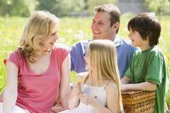 Familie, die draußen mit dem Picknickkorblächeln sitzt