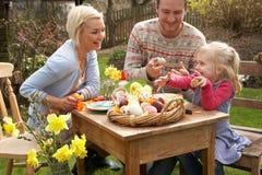 Familie, die draußen Ostereier auf Tabelle verziert Stockbild