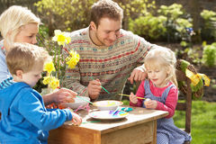 Familie, die draußen Ostereier auf Tabelle verziert Lizenzfreie Stockbilder