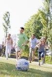 Familie, die draußen Fußball spielt und Spaß hat Stockfotos