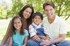 Familie, die draußen lächeln sitzt Lizenzfreie Stockfotos