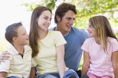 Familie, die draußen lächeln sitzt Lizenzfreie Stockfotografie
