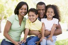 Familie, die draußen lächeln sitzt Stockbild