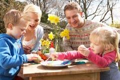 Familie, die draußen Ostereier auf Tabelle verziert Lizenzfreie Stockfotos