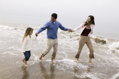 Familie, die durch Brandung auf Strand geht Lizenzfreies Stockfoto