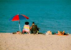 Familie, die durch das Meer sich entspannt Stockbilder