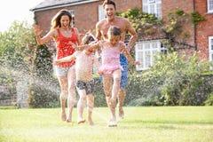 Familie, die durch Garten-Sprenger läuft Stockbild