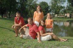 Familie, die durch Teich aufwirft stockbilder