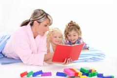 Familie die een boek samen leest Stock Foto