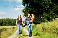 Familie die een gang dragend kind heeft Stock Foto's