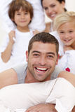 Familie die een hoofdkussenstrijd in bed heeft Stock Afbeelding