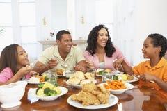 Familie die een Maaltijd heeft thuis Stock Foto's