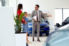 Familie die een nieuwe auto in de zaal van het autohandel drijven kopen stock afbeeldingen