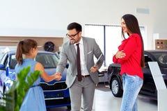 Familie die een nieuwe auto in de zaal van het autohandel drijven kopen royalty-vrije stock afbeeldingen