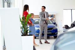 Familie die een nieuwe auto in de zaal van het autohandel drijven kopen royalty-vrije stock foto
