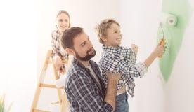 Familie die een ruimte samen schilderen stock foto's