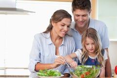 Familie die een salade voorbereidt Stock Afbeelding