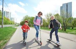 Familie die een skateboard en een autoped berijden Stock Foto's