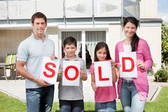 Familie die een verkocht teken buiten hun huis houdt Royalty-vrije Stock Afbeeldingen
