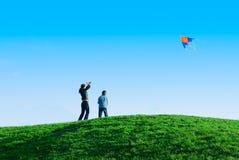 Familie die een vlieger speelt Stock Afbeeldingen