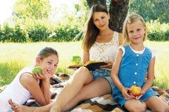 Familie, die ein Buch auf einem Picknick liest Lizenzfreie Stockfotografie