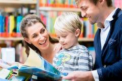 Familie, die ein Buch in der Bibliothek liest Stockfotos
