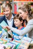Familie, die ein Buch in der Bibliothek liest stockbilder