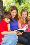 Familie, die ein Buch liest lizenzfreies stockbild