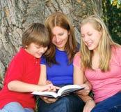 Familie, die ein Buch liest lizenzfreie stockfotos