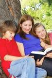 Familie, die ein Buch liest lizenzfreies stockfoto