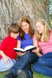 Familie, die ein Buch liest stockfotos