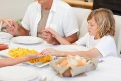 Familie, die ein Gebet vor Abendessen sagt