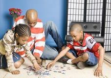 Familie, die ein Puzzlespiel tut Lizenzfreie Stockfotografie