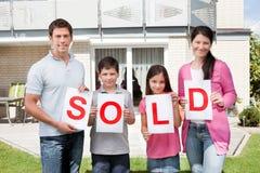 Familie, die ein Verkaufszeichen außerhalb ihres Hauses anhält Lizenzfreie Stockbilder