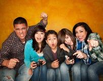 Familie, die ein Videospiel spielt Lizenzfreie Stockfotos