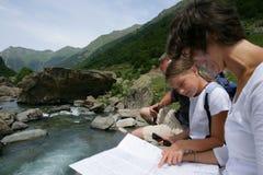 Familie, die eine Karte durch einen Fluss betrachtet Stockfotografie