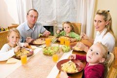 Familie, die eine Mahlzeit zusammen hat Stockbilder