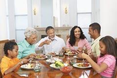 Familie, die eine Mahlzeit zusammen zu Hause hat stockfoto