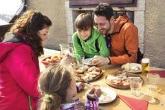 Familie, die in einem Chalet im Berg zu Mittag isst lizenzfreie stockbilder