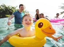 Familie, die in einem Pool spielt lizenzfreie stockfotos